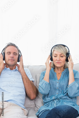 Couple relaxing and listening to music on the couch