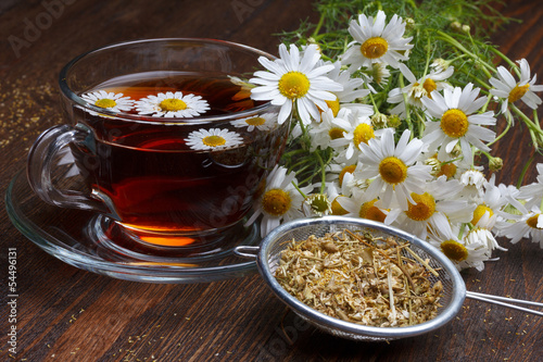 Chamomile tea and dried flowers on wooden table
