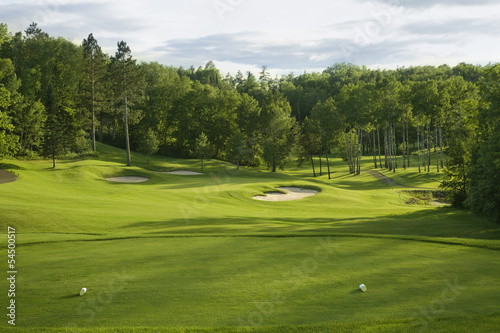 Photo Stands Golf Golf green with bunkers in afternoon sunlight
