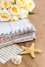 Stack Of Old Letters And Bouquet Of Pastel Yellow Roses On Wood
