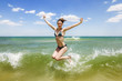 Girl jumping and splashing in the waves of the sea