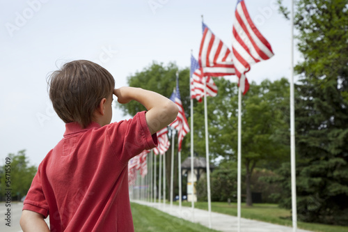 Tablou Canvas Boy salutes flags at Memorial Day display in a small town