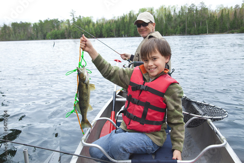 Fotografie, Obraz  Young fisherman proudly shows first walleye of the day