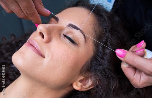 woman on facial hair removal threading procedure Fototapeta