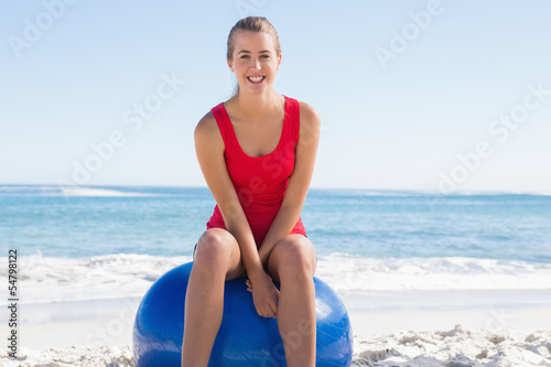 Fotobehang womenART Fit young woman sitting on exercise ball smiling at camera