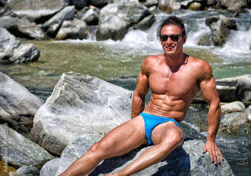 Deurstickers Akt Attractive young muscle man sitting on big rock by river water