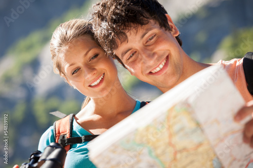 Fotografie, Obraz  Closeup of couple in the mountains looking at the map