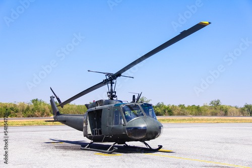 Tuinposter Helicopter Military helicopter (huey) at a base