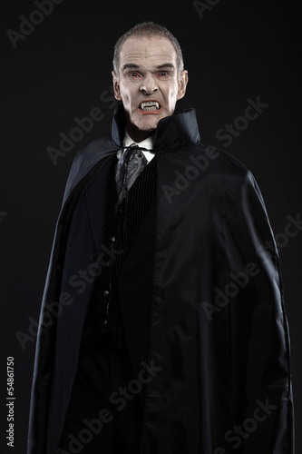 Photographie  Dracula with black cape showing his scary teeth. Vamp fangs. Stu