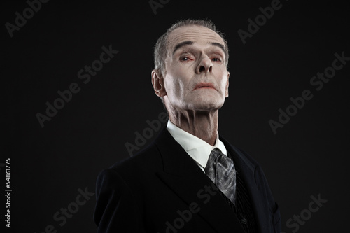 Fotografie, Obraz  Scary count dracula in black suit. Pale head. Studio shot agains