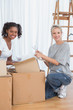 Cheerful friends unpacking boxes in new home