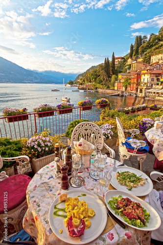 Romantic dinner scene of plated Italian food on terrace overlook Fototapeta