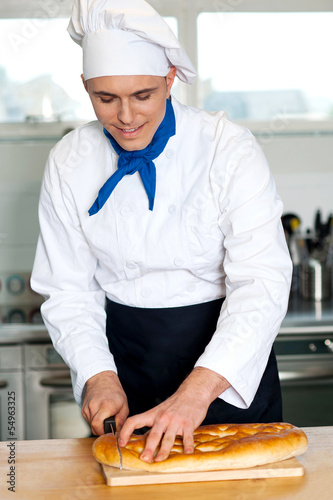Fototapety, obrazy: Chef cutting large bread loaf