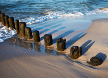 Remains Of Old Wooden Pier In The Sand Of Baltic Sea Coast
