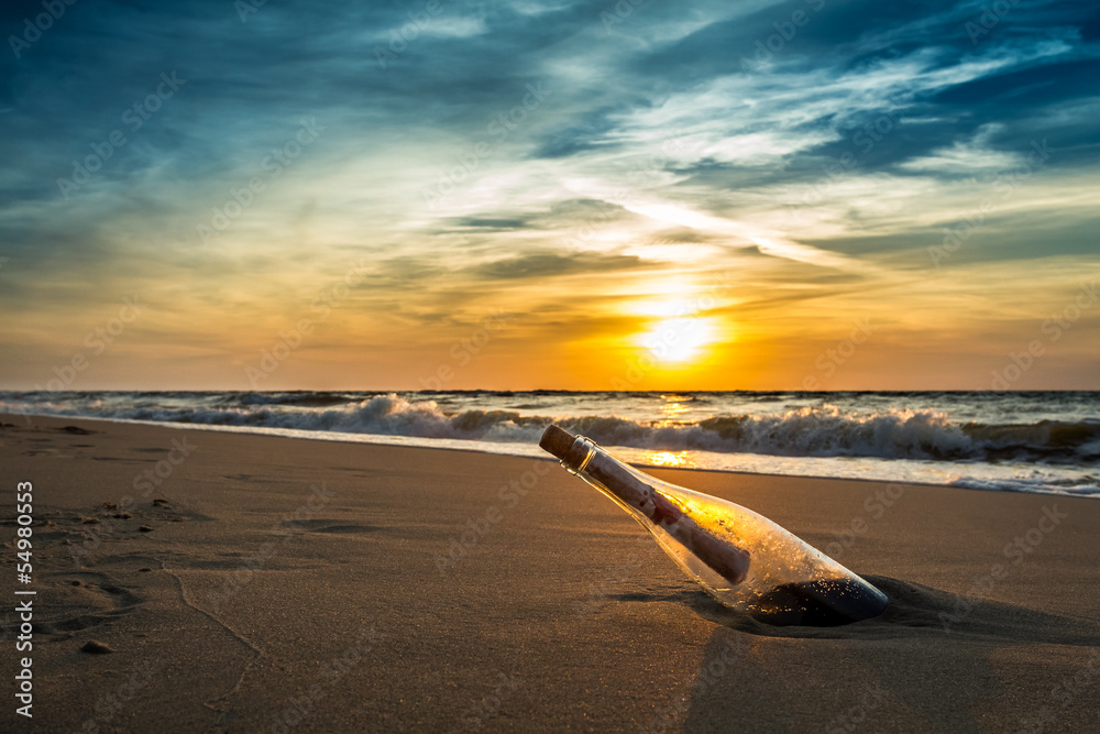 Fototapeta Message in a bottle on a beach against the setting sun