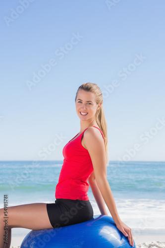 Fotobehang womenART Cheerful woman sitting on exercise ball looking at camera