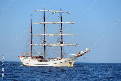 Türaufkleber Schiff old historical tall ship with white sails in blue sea