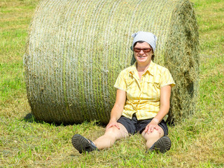Naklejka na ściany i meble Farmer sitting in front of hay bales