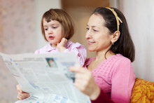 Mature Woman And Child Reading Newspaper