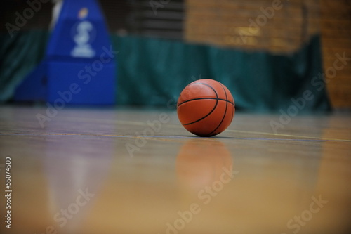 Foto  basketball ball and net on black background