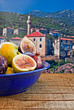 Bowl of fresh figs on rustic wooden table against village backgr