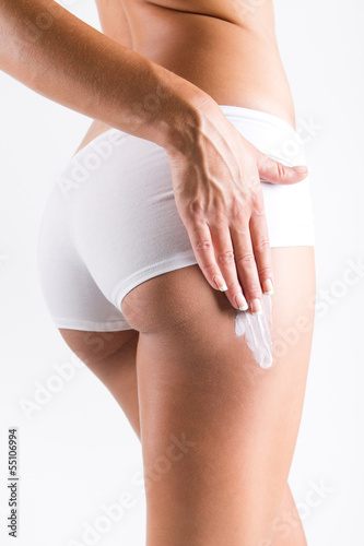 Fototapeta Woman applying cream on legs obraz na płótnie
