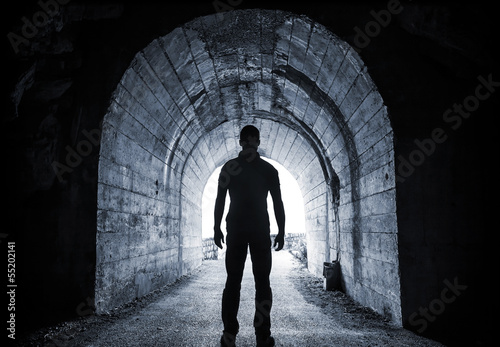 Fotografie, Obraz  Man stands in dark tunnel and looks in glowing end