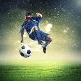 Fototapeta Młodzieżowe - football player striking the ball
