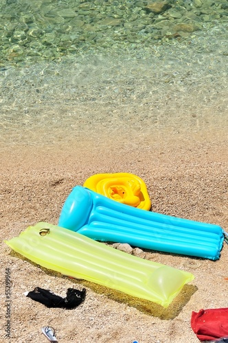 Fotografie, Obraz  Colorful floating beds with beach items in pebbly beach