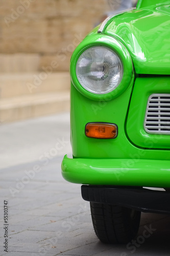 Photo head light of a East-German plastic vintage car. Green Trabant