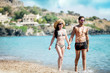 Attractive couple is walking through the water at the beach