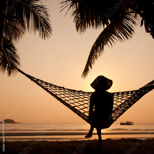 Poster  woman in hammock enjoying sunset on the beach