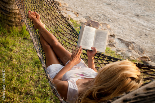 Deurstickers Ontspanning Woman reading in a hammock on the beach