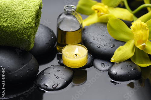 bottle of essential oil with two orchid and candle on pebbles