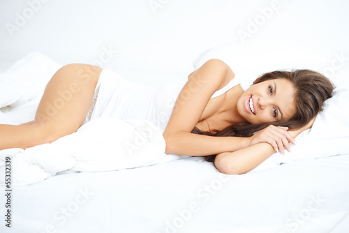 Vivacious młoda kobieta w łóżku