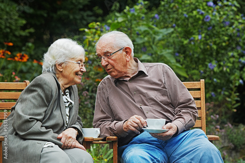 Photo  aged couple on the garden bench
