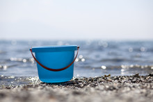 Blue Plastic Bucket On The Gravel Beach