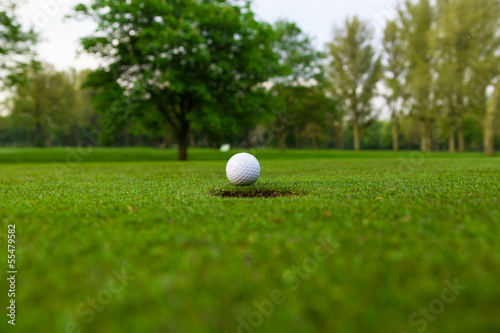 Poster Golf golf ball on lip of cup.