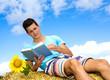 Sommer: Junger Mann genießt das Lesen auf Heuballen