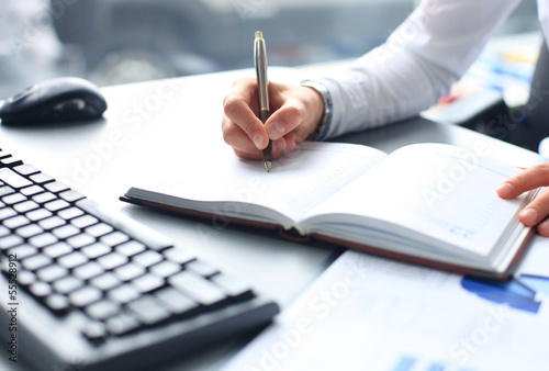 Businesswoman makes a note in notebook Canvas Print