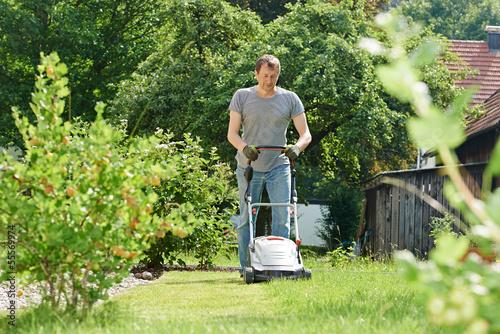Papiers peints Jardin man mowing lawn in backyard