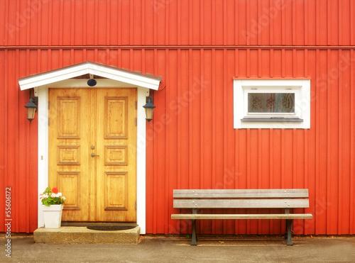 Papiers peints Scandinavie Wooden yellow door in orange colored building