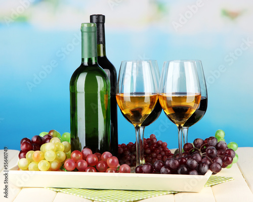 Fototapety, obrazy: Wine bottles and glasses of wine on tray, on bright background