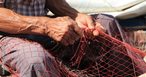 Fotografía  Mani al lavoro su una rete da pesca