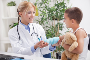 doctor examines, young boy wearing a blue cast