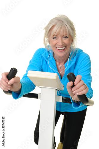 Fotografie, Obraz  Sportliche Seniorin auf dem Hometrainer hört Musik