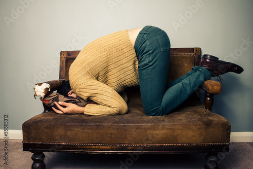 Fotografía  Young man burying his face in old sofa