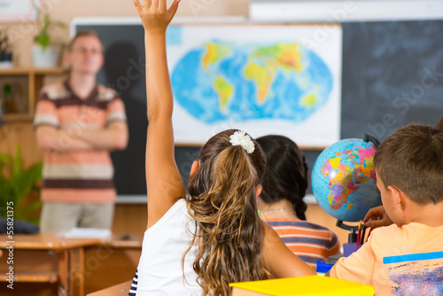 Fotografía  Schoolgirl rising her hand at geography lesson