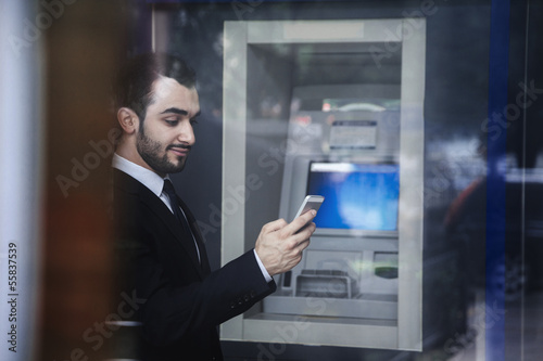 Fotografia, Obraz Smiling young businessman standing in front of an ATM and looking at his phone