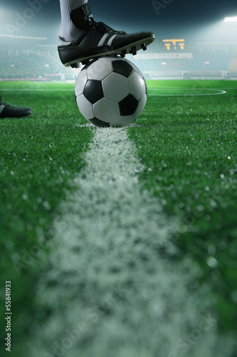 Photo  Close up of foot on top of soccer ball on the line, side view, stadium